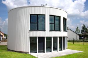 La maison ronde à ossature bois et bardage de tôle ondulée blanche. L'ensemble des cloisons étant rondes, ce sont les cloisons intérieures qui accueillent le mobilier.